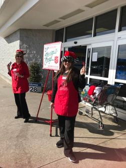 2 ladies ringing the salvation army bell in front of store