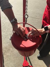 Hands putting money in a red bucket